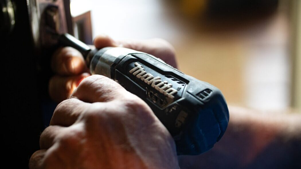 Two hands using a Makita drill