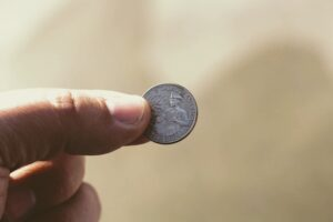 A hand pinching a quarter dollar coin