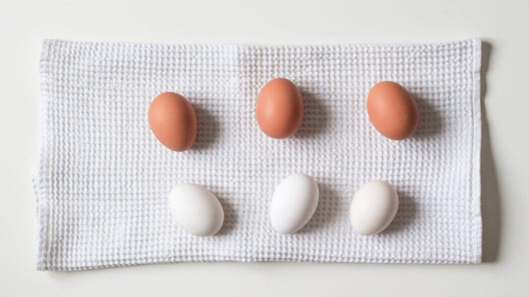 Three brown and three white eggs sitting on a kitchen towel