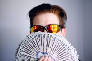 A person in sunglasses holding a splayed out stack of one hundred dollar bills
