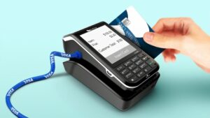 A person sliding a card through a card reader
