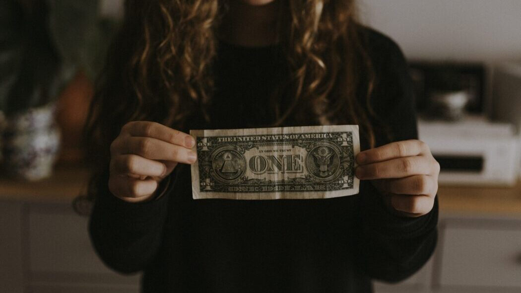 A person holding up a one dollar bill