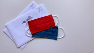 A red facemask and a blue facemask on top of voting envelopes