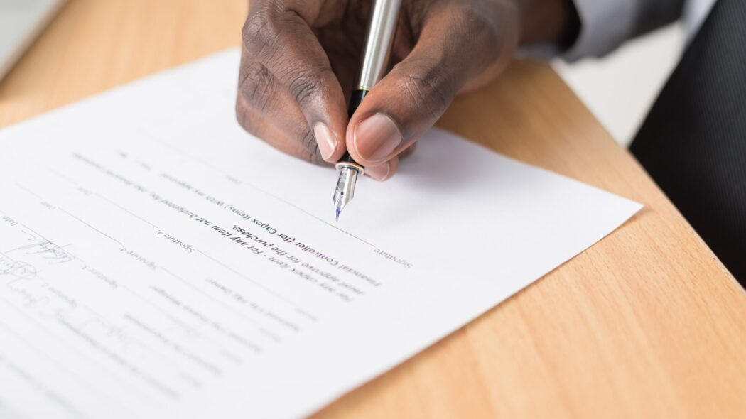 A person signing a document on a table