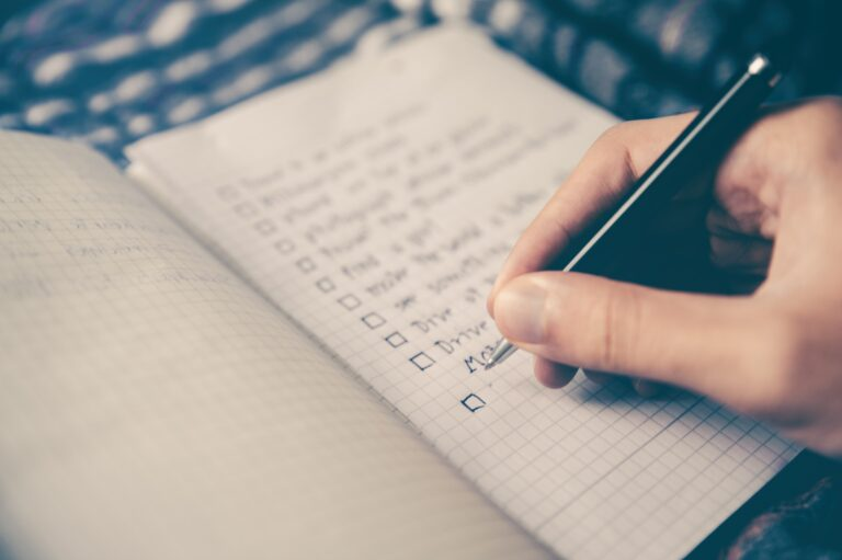 A hand writing a checklist in a notepad