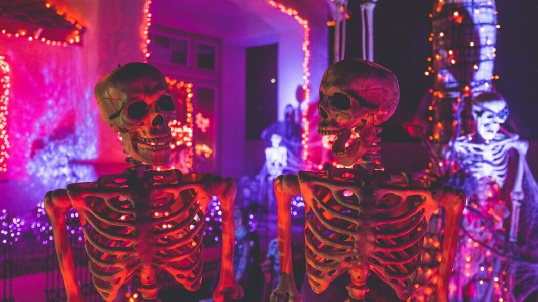 A halloween scene with three skeletons and lights