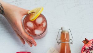 A hand grabbing a glass of kombucha with ice and a lemon slice