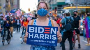 A female with a mask standing in a street holding a Biden/Harris sign