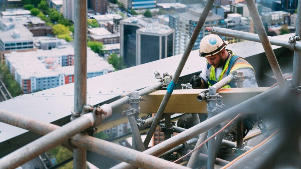 A construction working working high up on a high rise building