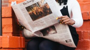 A female reading the New York Times on an orange brick entrance stairway