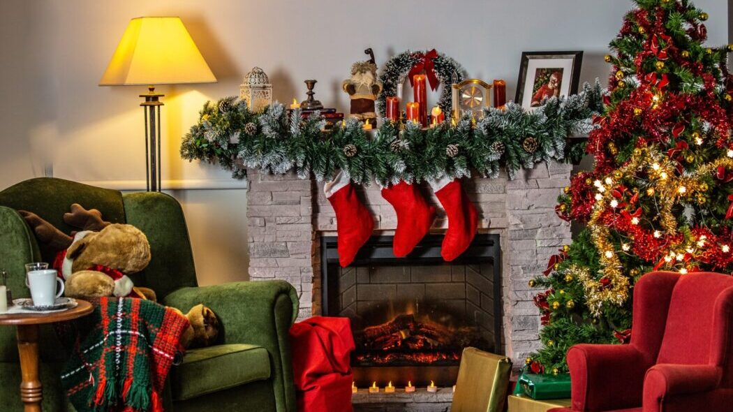 A living room with a green and red chair decorated for the holidays