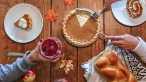 Looking down on a table with pumpkin pie, bread and orange leaves