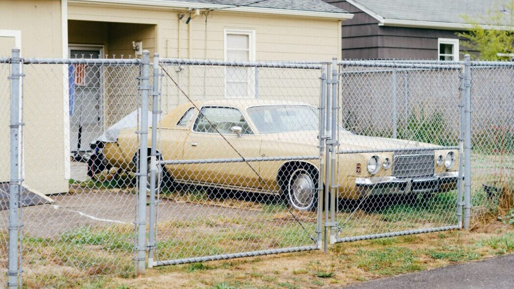 An old yellow car parked in front of a yellow house behind a chain link fence