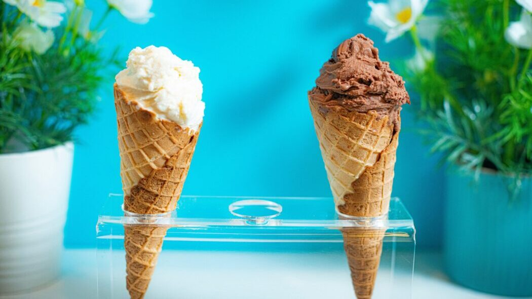 One vanilla and one chocolate ice cream cone in a display