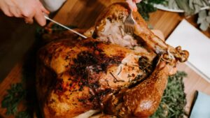 A person carving a turkey on a table