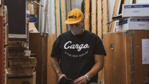 A man in a black shirt and orange hat working in a workshop