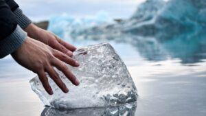 Two hands on a large block of ice next to icebergs