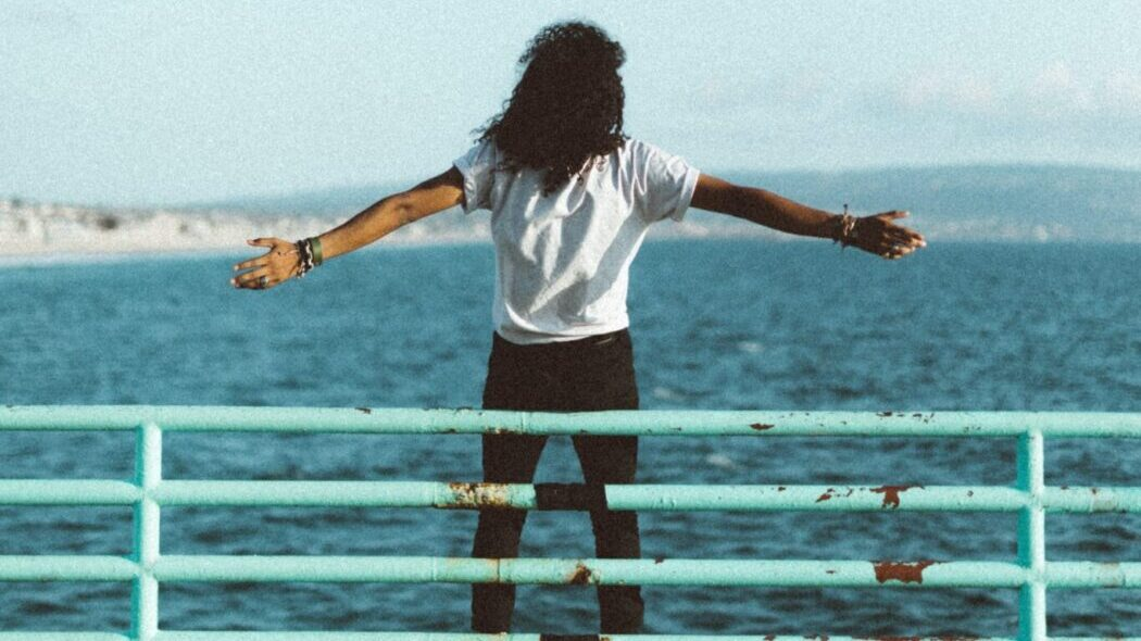 A person with long hair standing with their arms out in front of a body of water