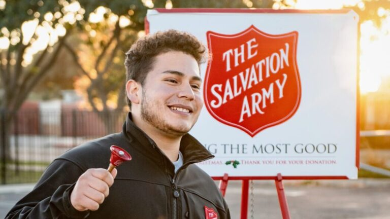 A person ringing a bell in front of a Salvation Army sign