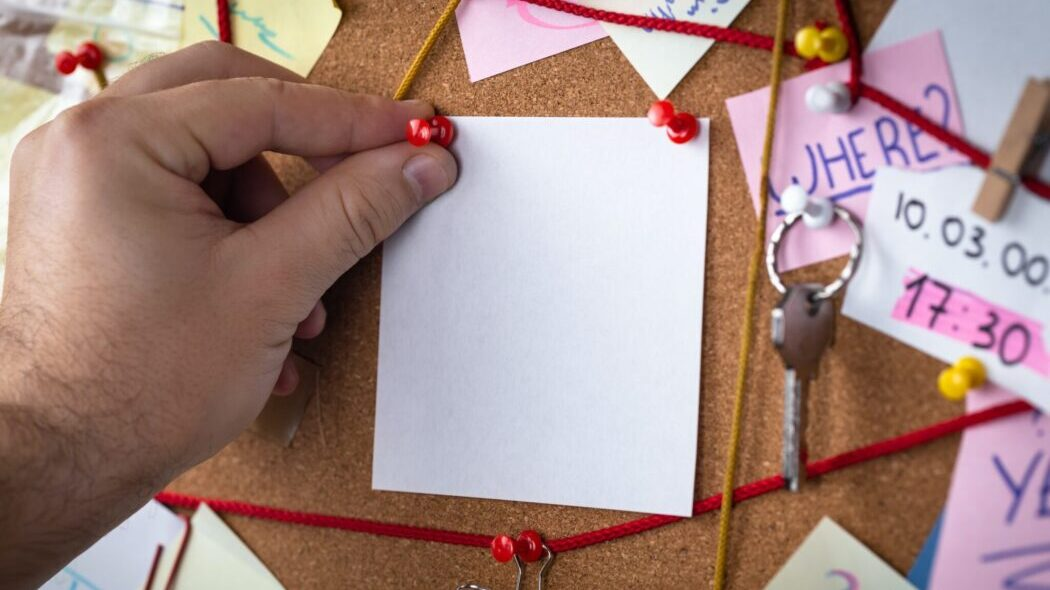 A hand pinning a black piece of paper to a cork board