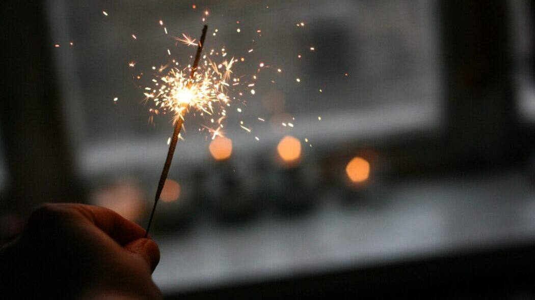 A person holding a lit sparkler inside a room