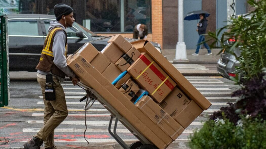 A UPS man pushing a fully loaded dolly of packages