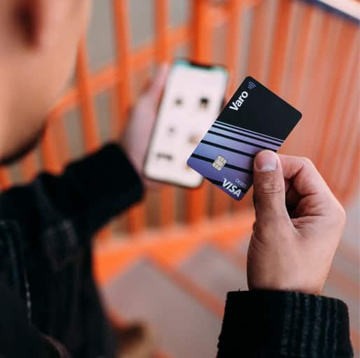 person holding phone and varo card