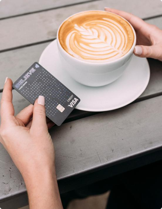 person holding card and coffee