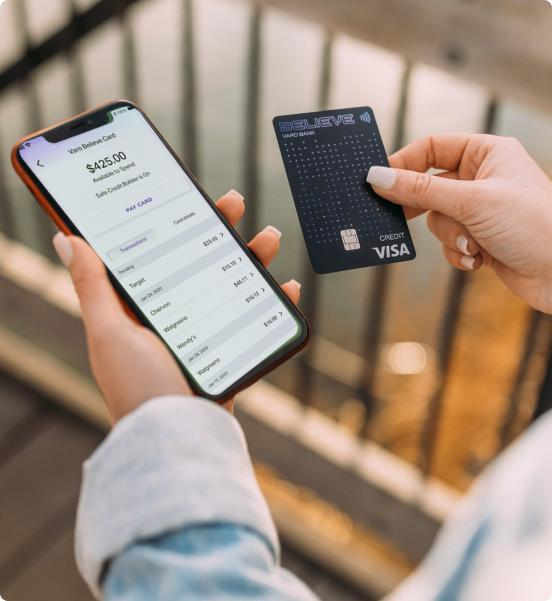 person holding varo card and phone with varo bank app